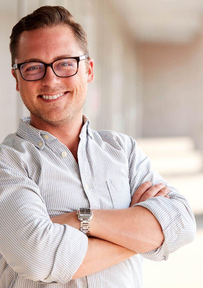 portrait-of-smiling-male-school-teacher-standing-i-7KLZDMS.jpg